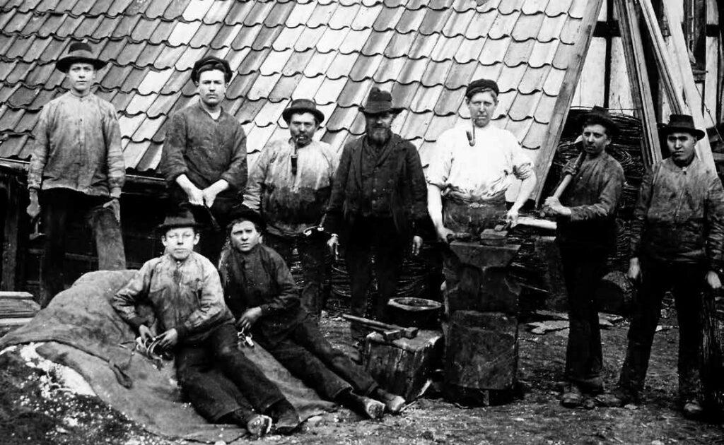 Technischer Alltag aus dem Sauerland kurz vor dem ersten Weltkrieg: Die Mannschaft einer Werkstatt am Maiwormshammer, zwischen (Alt-) Listernohl und Ewig, präsentiert sich stolz mit den Topf- und Pfannengriffen, wie sie aus der Drahtrolle produziert werden.