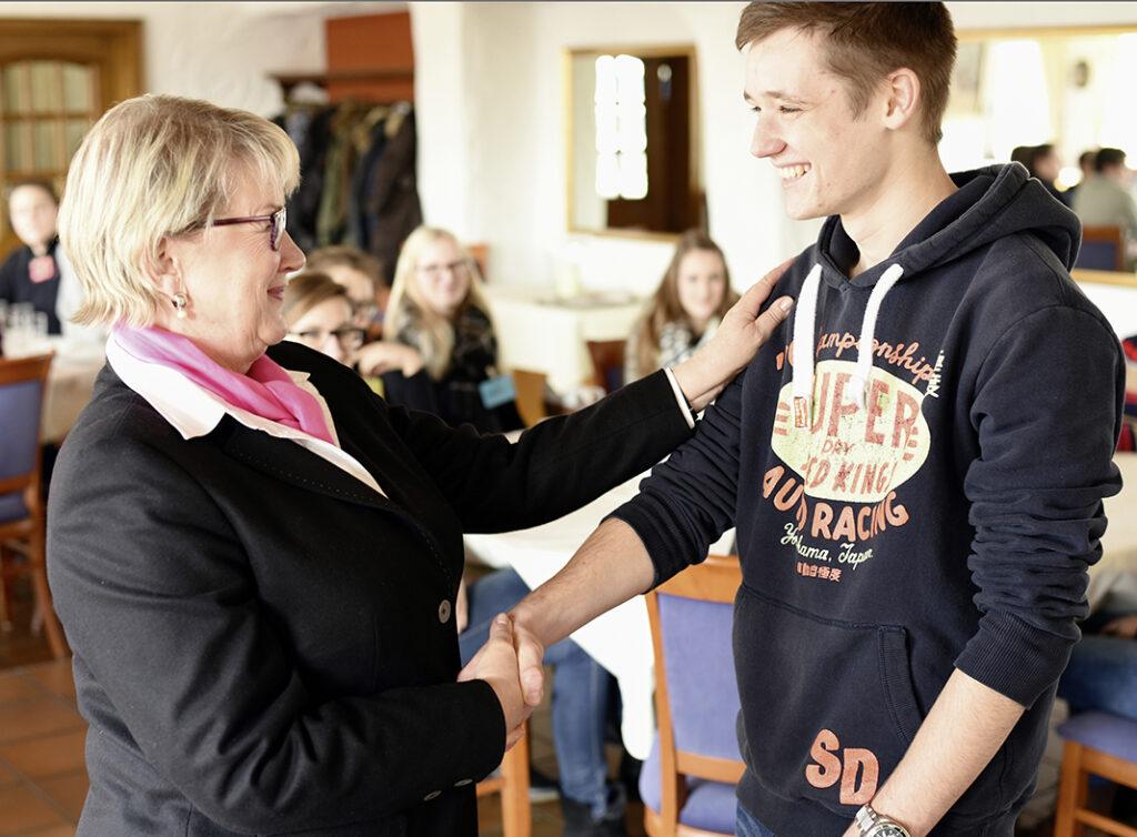 """""""Anschauen bei der Begrüßung und möglichst lächeln, aber im Geschäftsalltag nicht zu  viel Körperkontakt."""" Lis Droste (links) zeigte den St.-Ursula-Schülern, wie man es richtig macht."""
