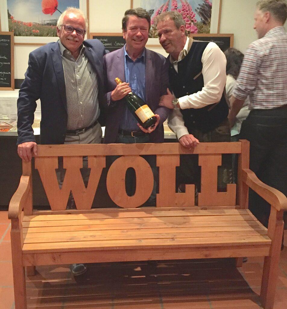 Jaap Neele aus den Niederlanden (Mitte) bekam als Dankeschön für seine langjährige Teilnahme und Unterstützung bei den Sauerland Open sowie seine unterhaltsamen Reden bei der Siegerehrung, die immer mit WOLL enden, eine WOLL-Bank und eine Flasche WOLL-Sekt überreicht.