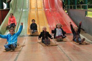 Begeisterte und strahlende Kinder auf der Regenbogen-Wellen-Rutsche – einer der Highlights im Erlebnispark Ketteler Hof