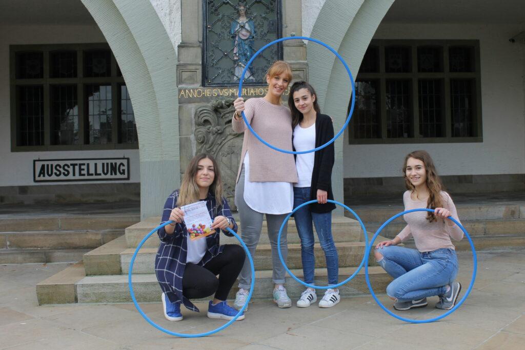 Verkäufer blicken von ihren Ständen auf, vorbeigehende Menschen halten inne und schauen zum Rathaus; ihre Blicke folgen den wirbelnden blauen Ringen. Der blaue Ring ist das offizielle Zeichen des Weltdiabetestages, mit dem am 14. November verstärkt auf den Diabetes Typ-2 aufmerksam gemacht werden soll. Das Städt. Krankenhaus Maria-Hilf Brilon unterstütze dieses Anliegen am vergangenen Samstag  mit einer Hula-Hoop-Choreografie auf dem Marktplatz. Die Briloner Bürger sollten dafür sensibilisiert werden, dass eine gesunde Ernährung und körperliche Betätigung Diabetes-Typ-2 vorbeugen können. Gleichzeitig lud das Briloner Krankenhaus die Bürger zu ihrem Diabetes-Aktionstag am 6.11.2016 in das Foyer des Krankenhauses ein. Birgit Schrowange konnte als Schirmherrin gewonnen werden (weitere Infos im Text). Auf dem Bild v.l.: Adriana Oliveira, Christin Gördes, Alina Varela und Rafaela Franco. Foto: Julia Gördes, Städt. Krankenhaus Maria-Hilf Brilon