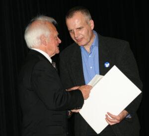 Pater Klein überreicht Peter Bürger die Urkunde für die Verleihung des Rottendorf Preises an Peter Bürger