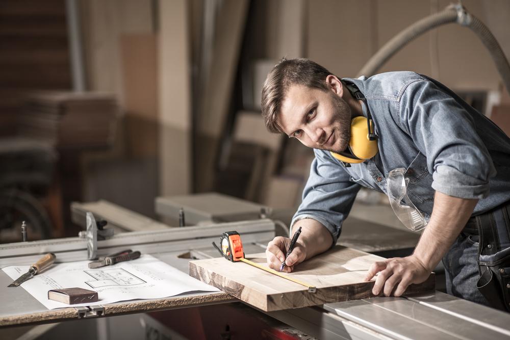 Lächelnder Schreiner hat ein Maßband auf einem Holzstück liegen und zeichnet etwas mit einem Stift ein.