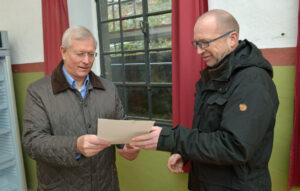 Der Präsident der NRW-Stiftung Eckhard Uhlenberg (links) übergibt den Förderbescheid an den 2. Vorsitzenden des Bilsteintalvereins Bertram Mestermann (rechts) Foto: Christian Clewing