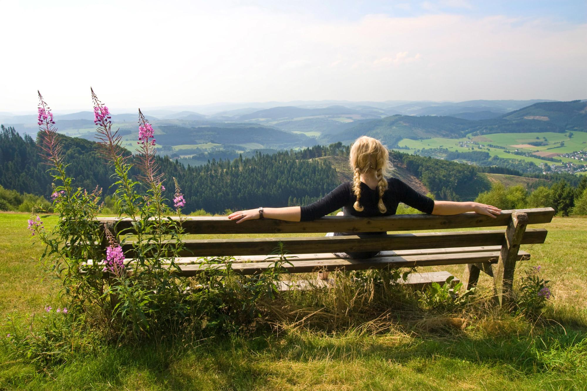 Eine Wanderin genießt bei ihrer Rast die Aussicht über die Sauerländer Landschaft. Foto: Sauerland-Tourismus e.V. / Sabrina Voss