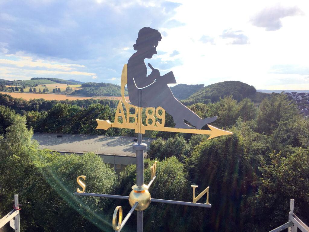 Die Wetterfahne - das Denkmal des Abiturjahrgangs 1989 - thront nun wieder auf dem Altbau des Gymnasiums der Benediktiner. Bildnachweis: Karl Thomas