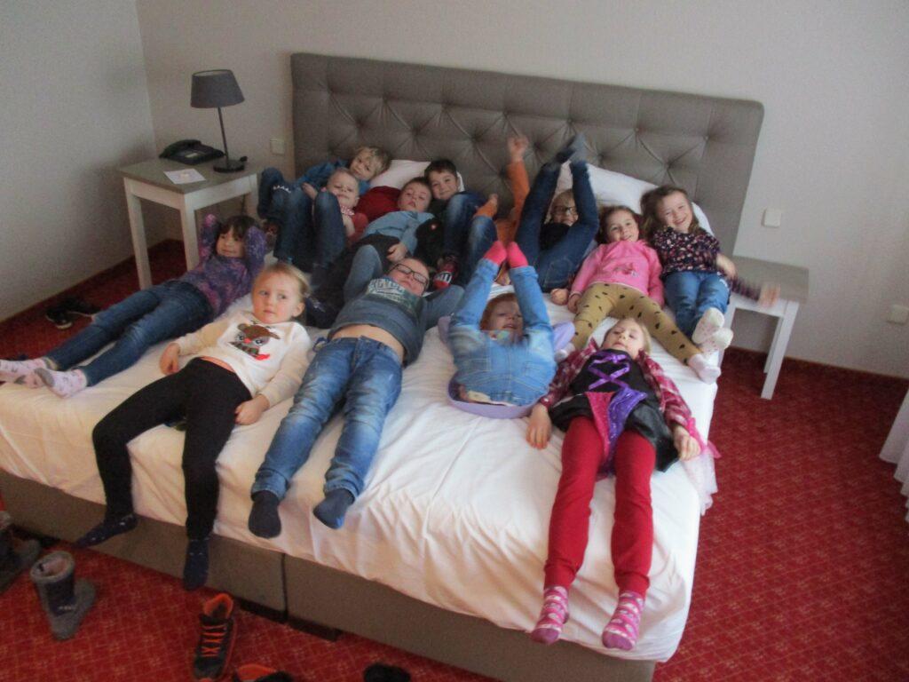 Geschafft! 13 müde Vorschulkinder verschnaufen auf dem kuschelweichen Bett