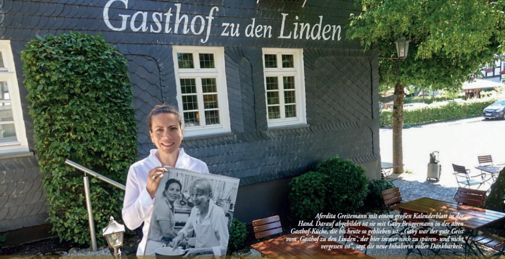 """Aferdita Greitemann mit einem großen Kalenderblatt in der Hand. Darauf abgebildet ist sie mit Gaby Brüggemann in der alten Gasthof-Küche, die bis heute so geblieben ist. """"Gaby war der gute Geist vom 'Gasthof zu den Linden', der hier immer noch zu spüren- und nicht vergessen ist"""", sagt die neue Inhaberin voller Dankbarkeit. Foto: giba"""