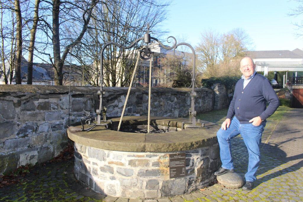 Peter Havestadt vor seinem 850 Jahre alten Brunnen, 1978 von ihm freigelegt und aufgebaut.