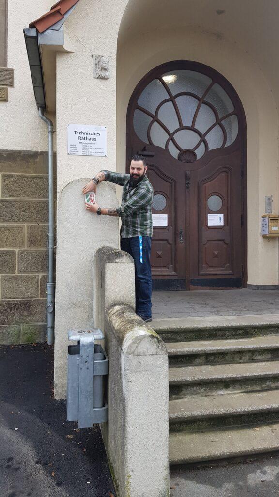 Alex Fiadeiro mit der Denkmalplakette des Landes NRW vor dem Technischen Rathaus, dem ältesten Schulbau der Stadt. Foto: Fabian Fischer