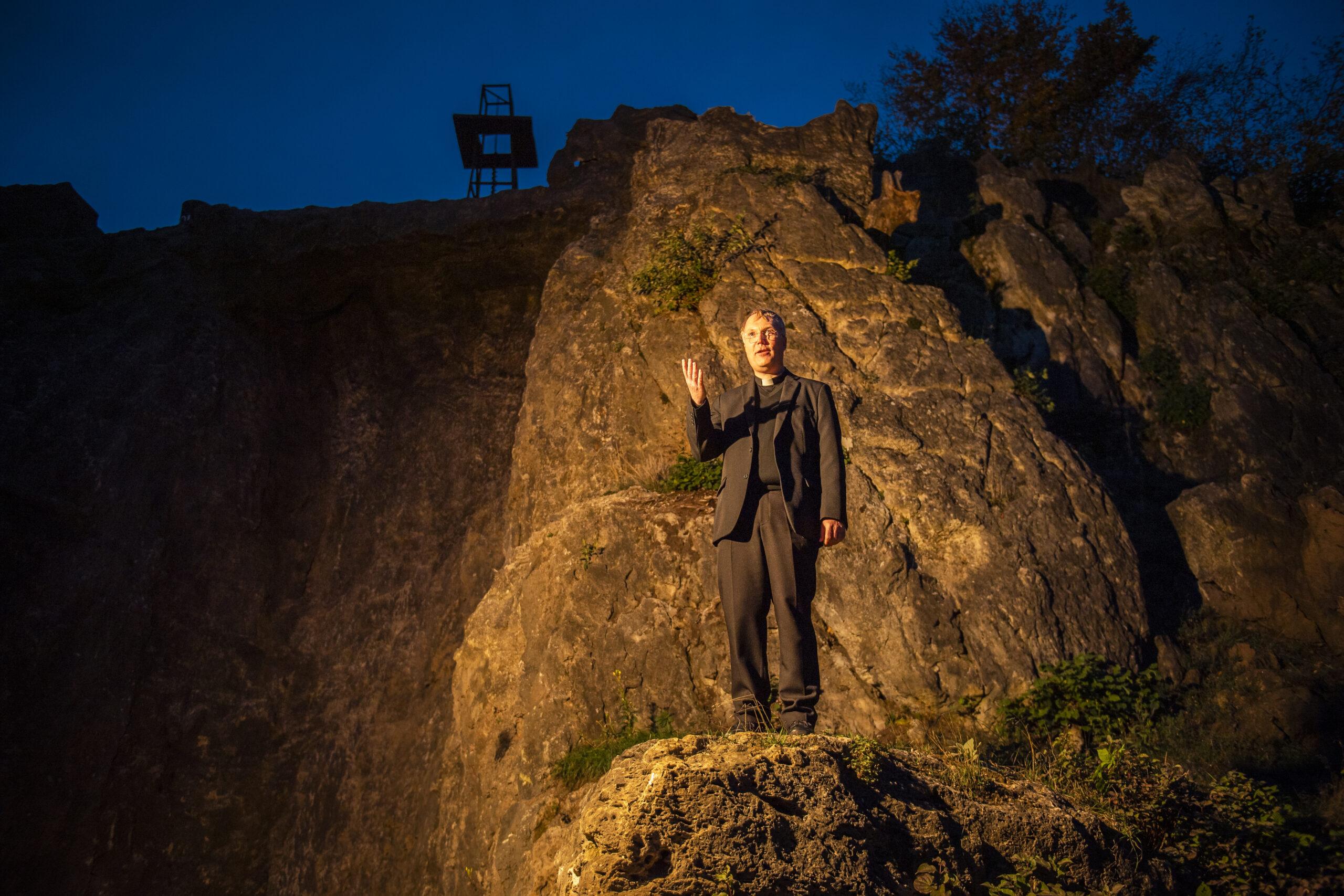 """Hier hätte er seine Weihnachts-Predigt gehalten: Pfarrer Christoph Gundermann vor dem Felsen der Elsper """"Karl-May-Bühne"""". Foto: Klaus-Peter Kappest"""