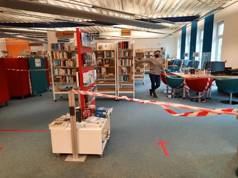 Noch ist hier das Absperrband - doch nach Ende der Einschränkungen ist die Stadtbücherei Olsberg - hier Bücherei-Mitarbeiterin Ludmilla Kinder - ein Ort zum Entdecken, Erleben und Wohlfühlen.