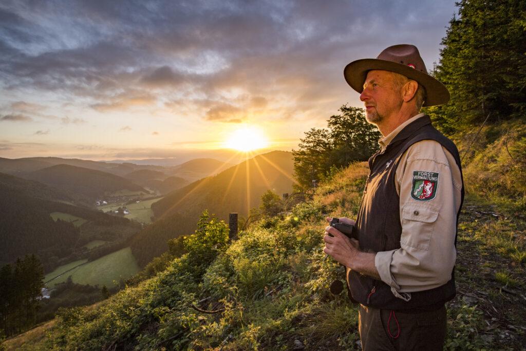 Südwestfalen Ranger Ralf Schmidt im Sonnenaufgang auf dem Rossnacken über dem Lennetal bei Lennestadt Saalhausen.