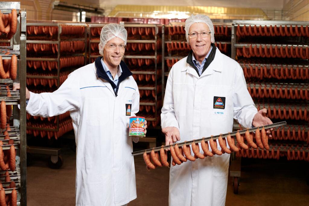 """Die geschäftsführenden Gesellschafter Tobias und Ulrich Metten freuen sich über das Jubiläum der """"Dicke Sauerländer"""" Bockwurst."""